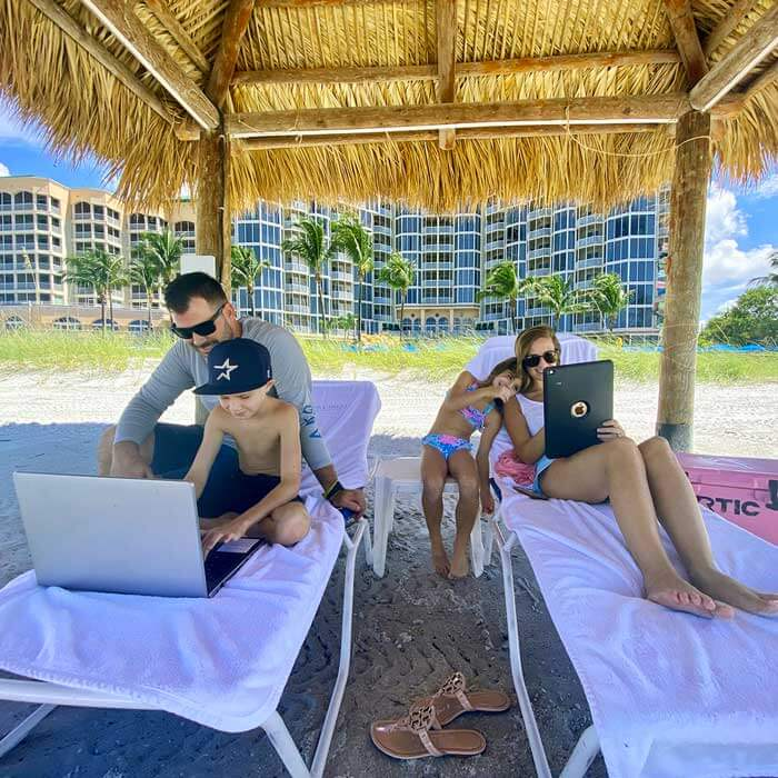 A family works and studies at the beach during a long-term stay at the resort