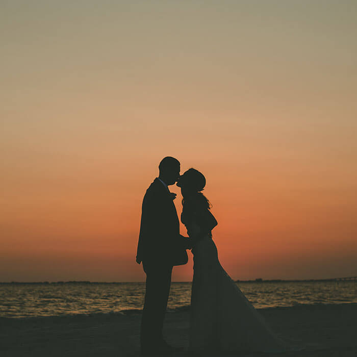 Newlyweds embrace by the ocean during sunset