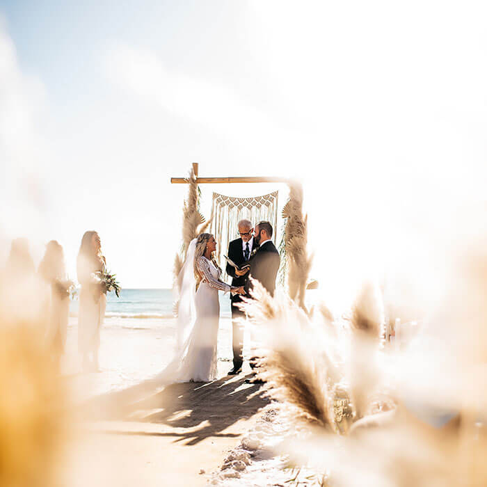 A couple shares their vows during a beachfront ceremony in Fort Myers Beach